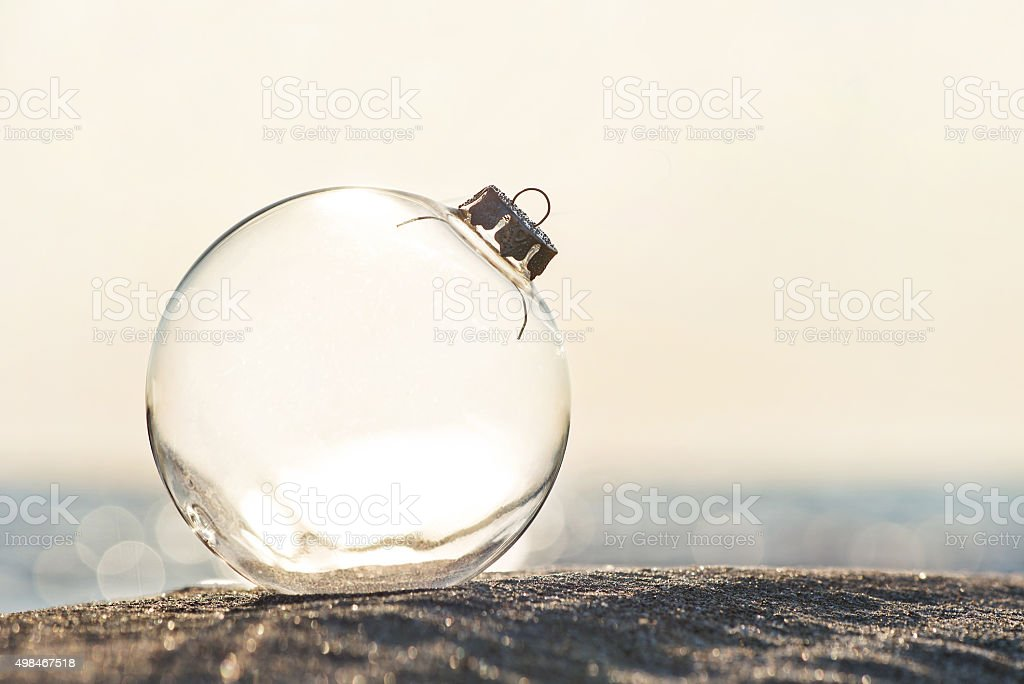 Christmas-tree decoration glass ball at ocean beach sunset time stock photo