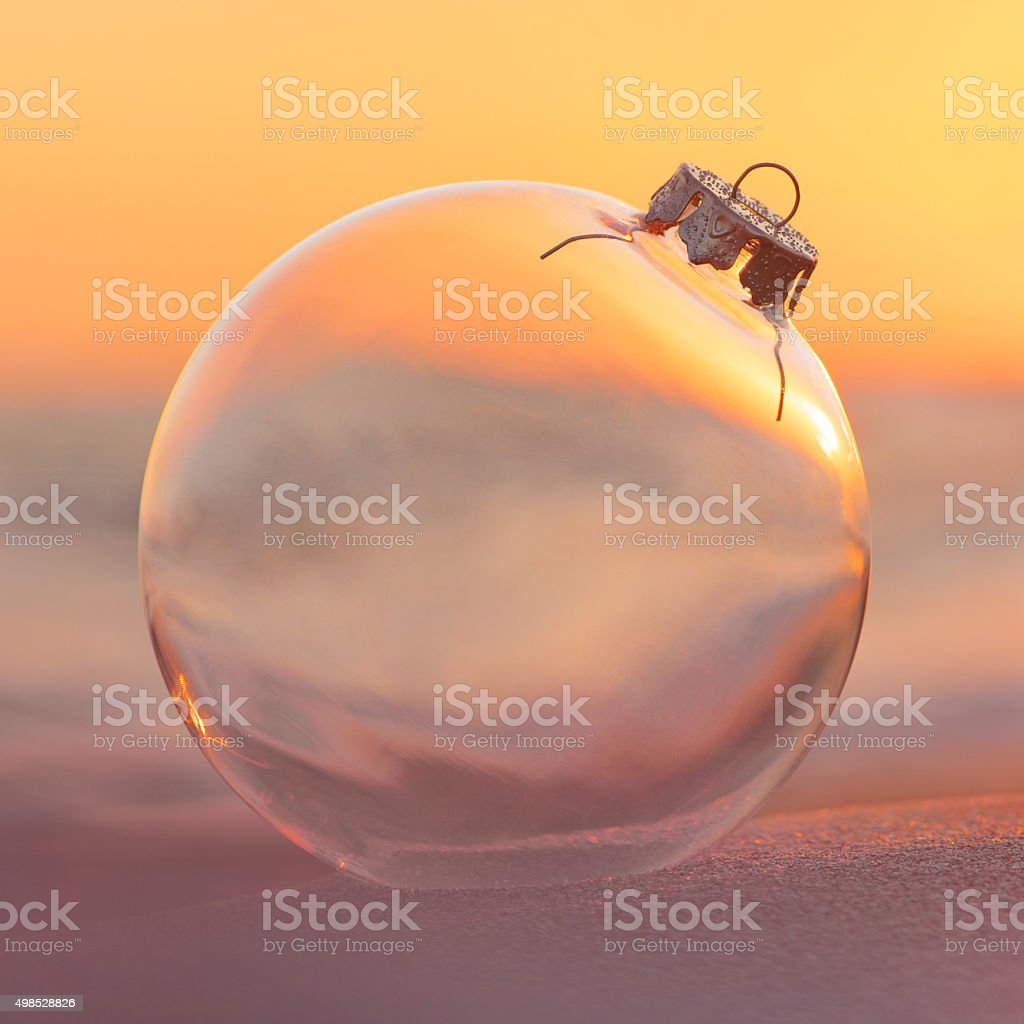 Christmas-tree decoration glass ball at sunset time ocean beach stock photo