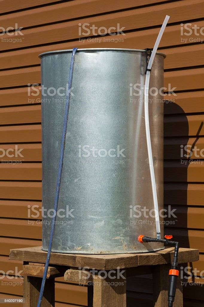 chrome barrel with hoses for irrigation stock photo