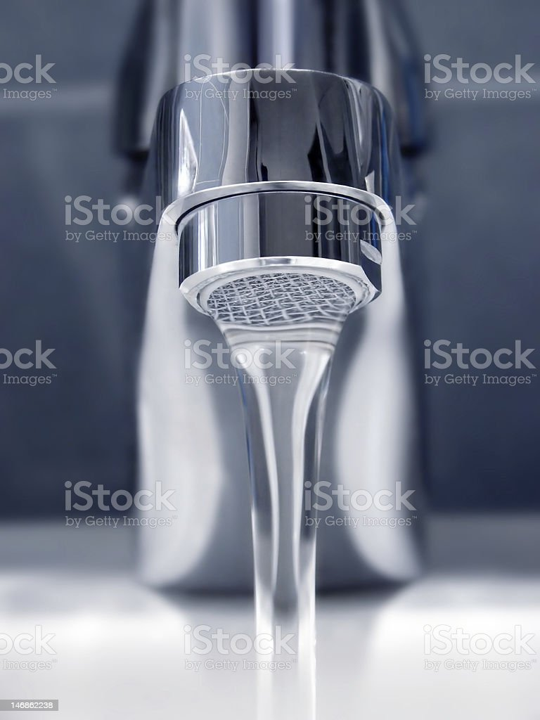 A chrome faucet flowing water smoothly stock photo