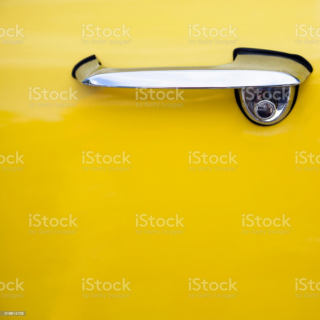 Chrome handle and partial yellow car door stock photo