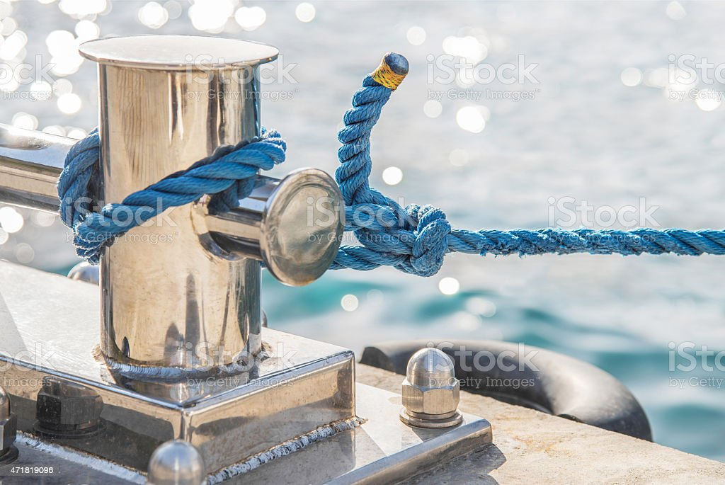 Chrome marina bollard with blue rope for mooring stock photo
