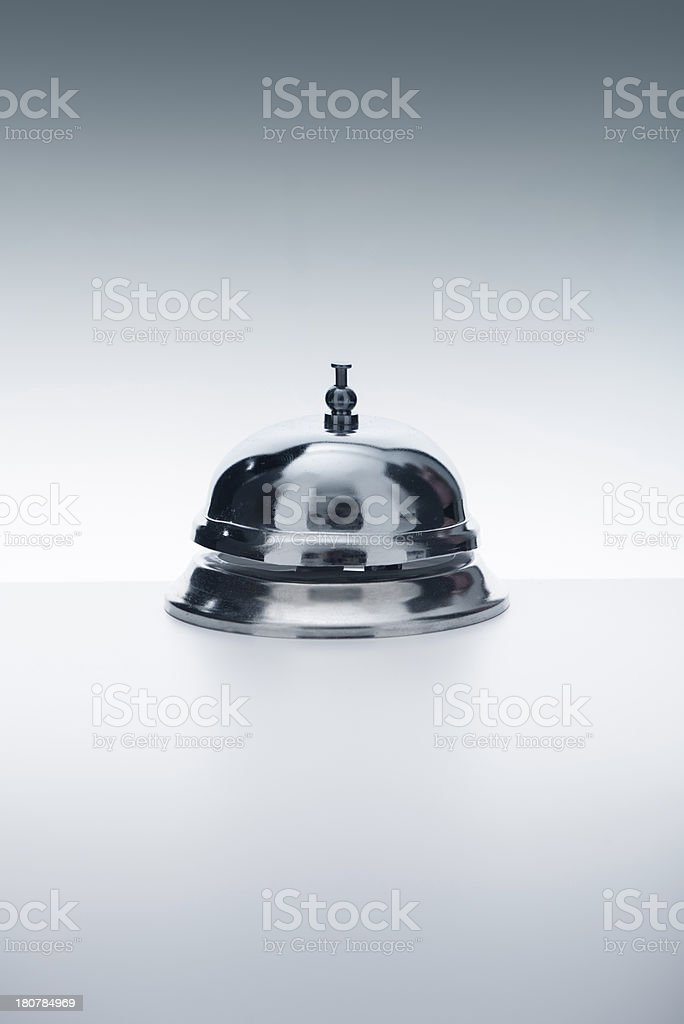 Chrome service bell atop a white surface and background royalty-free stock photo