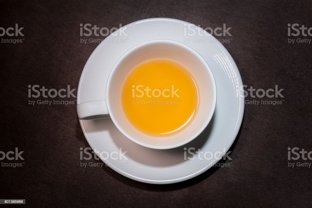 Chrysanthemum herbal tea in white cup on wooden table. stock photo