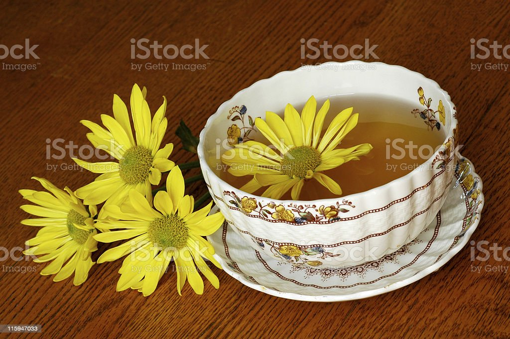 chrysanthemum tea in floral teacup on wood table royalty-free stock photo