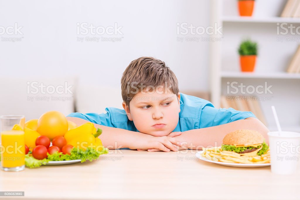Chubby boy is looking at junk food plate stock photo