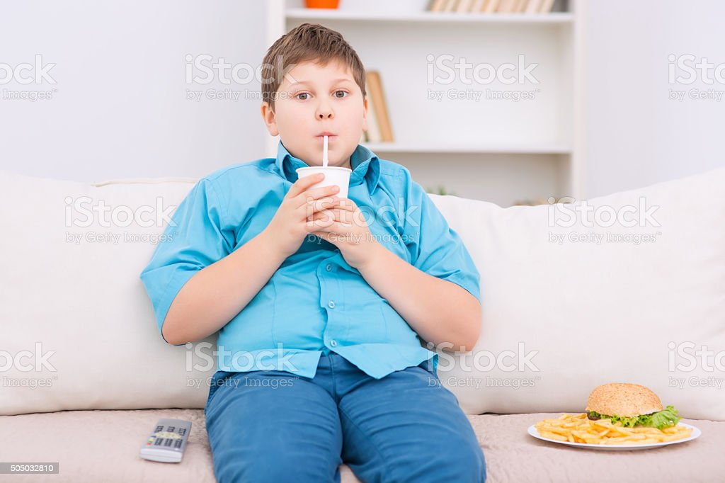 Chubby kid with junk food on the sofa stock photo