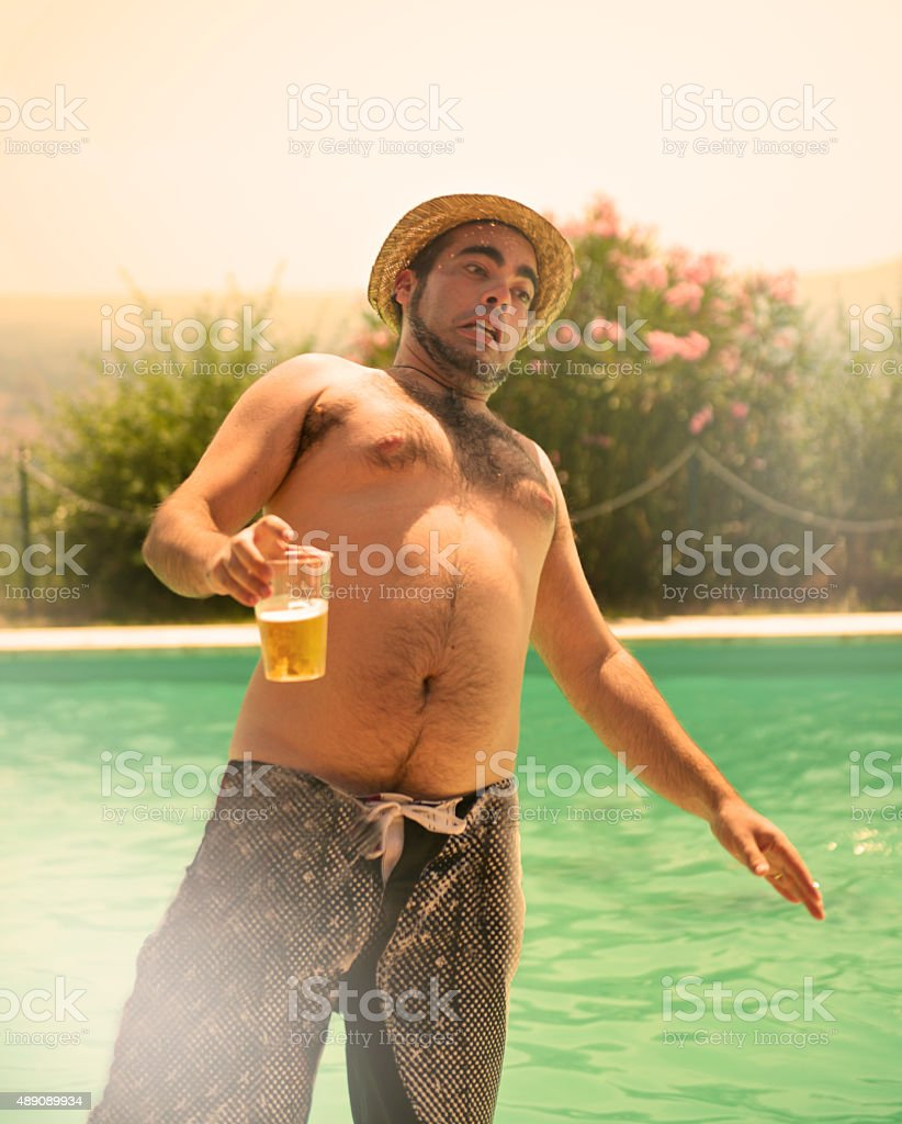 chubby young man with beer fall in the pool party stock photo
