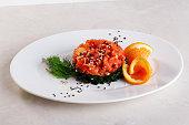 chuka salad, salmon, orange, black sesame, isolated on a plate