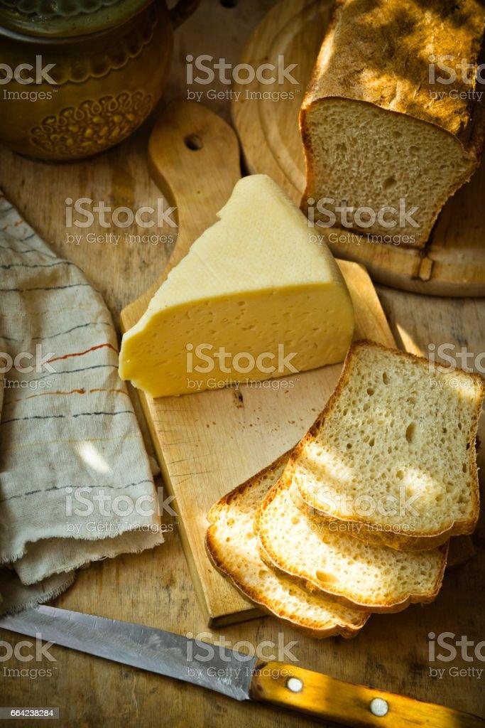 Chunk of cheese, loaf of sourdough bread on wood cutting board, linen napkin, rustic kitchen interior, sunlight flecks stock photo