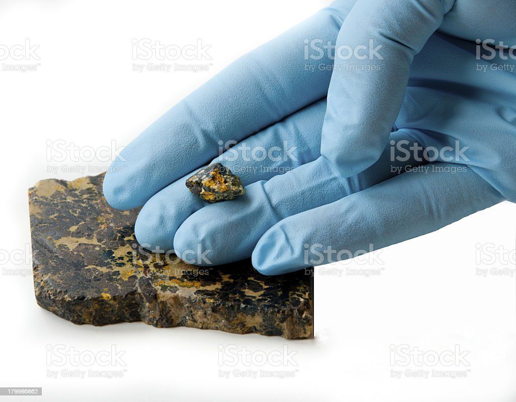 Chunk of uraninite in gloved fingers royalty-free stock photo