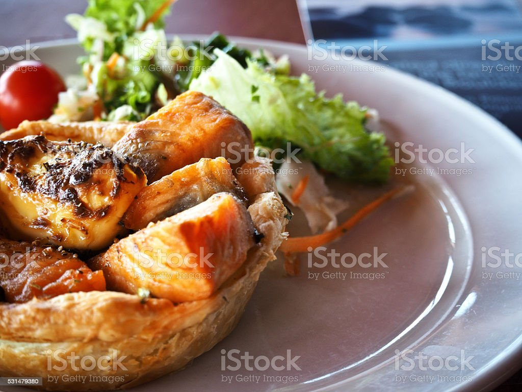 Chunky grilled salmon pie served with salad stock photo