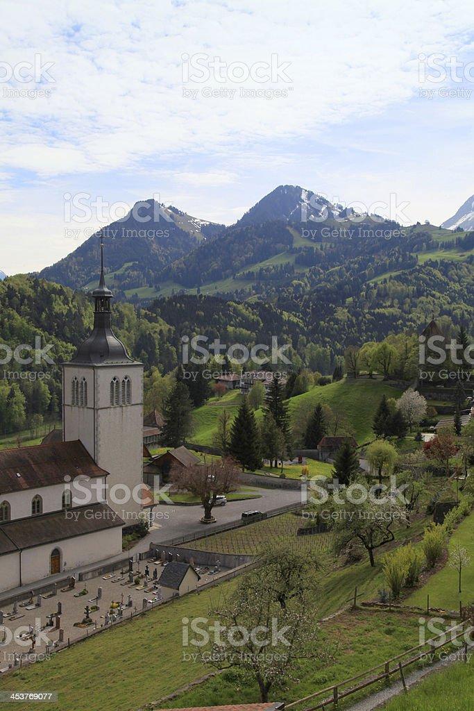 Church and Alps mountains, Gruyeres, Switzerland royalty-free stock photo
