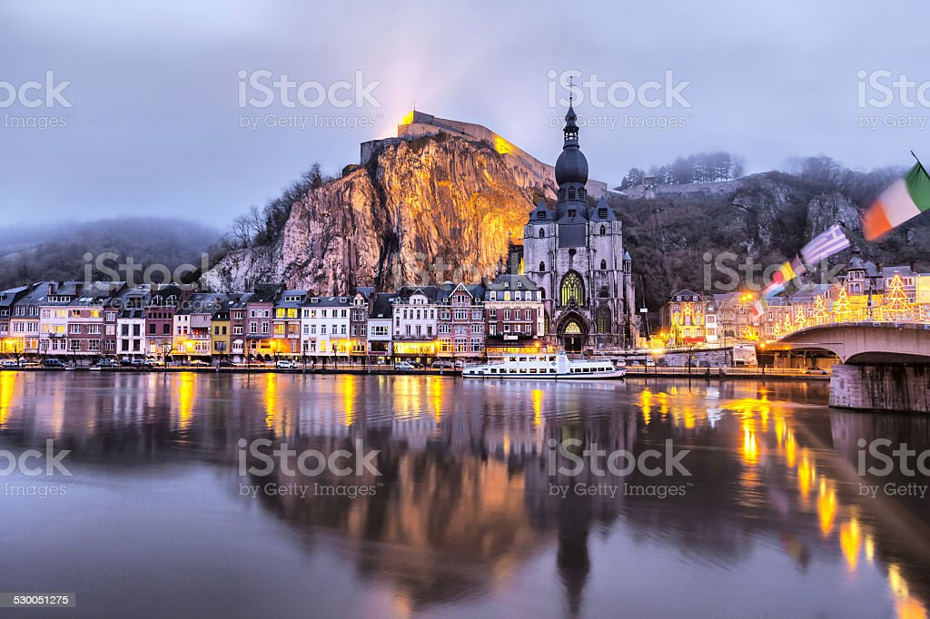 Church and cliff reflecting in river Meuse, Dinant stock photo