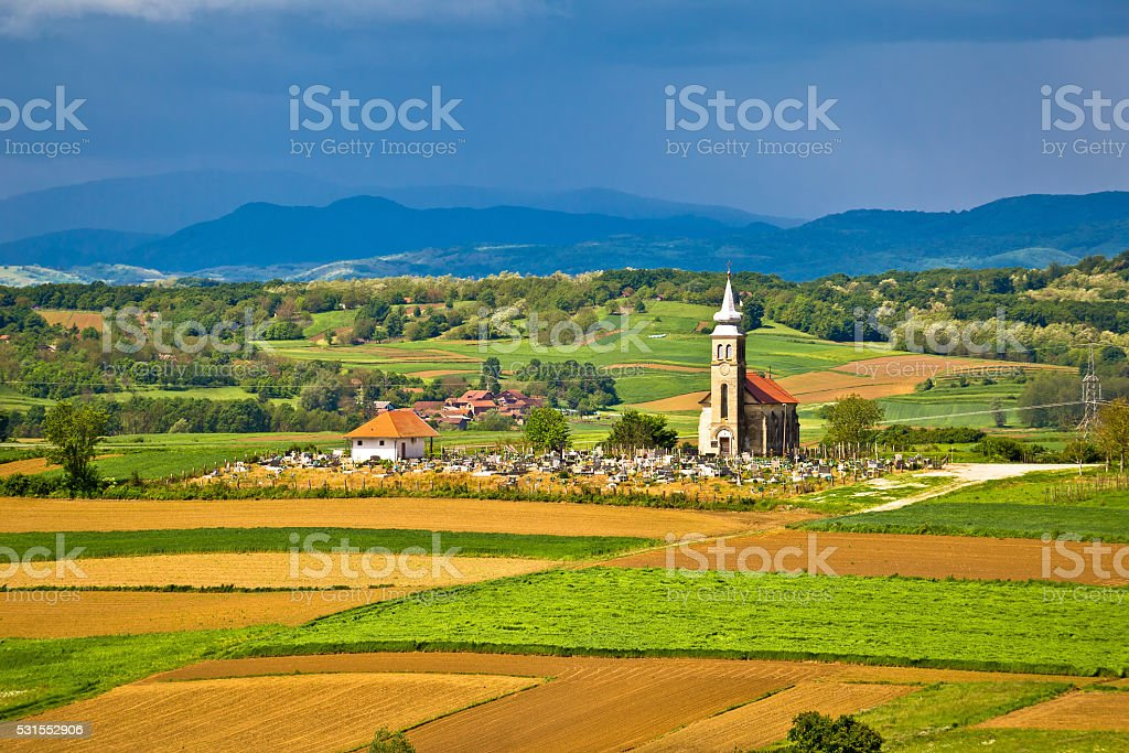 Church and graveyard on picturesque landscape stock photo
