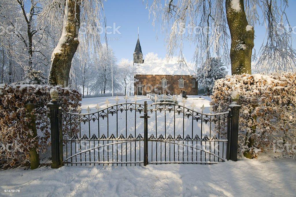 Église derrière une clôture dans le paysage d'hiver photo libre de droits