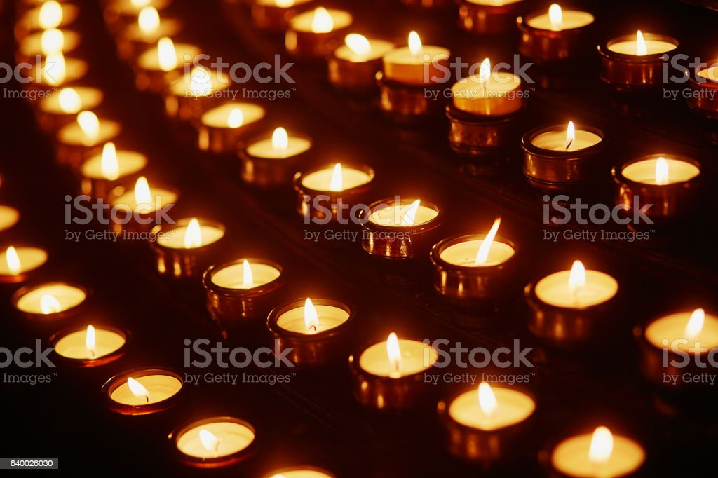 Church candles in yellow transparent chandeliers stock photo