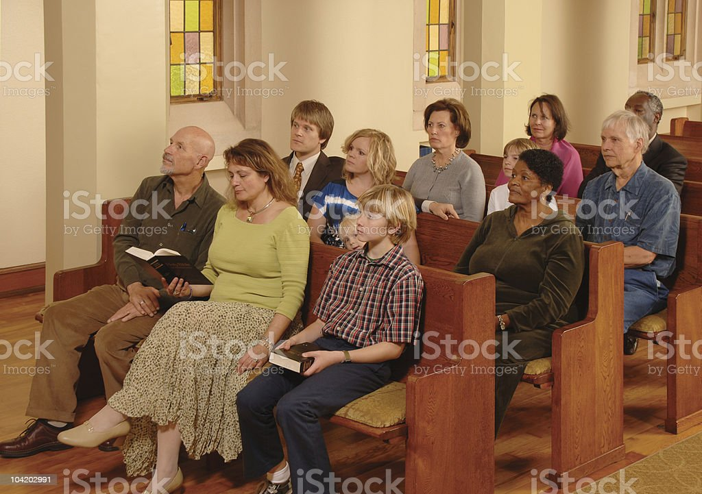 A church congregation sitting in pews listening to a sermon stock photo