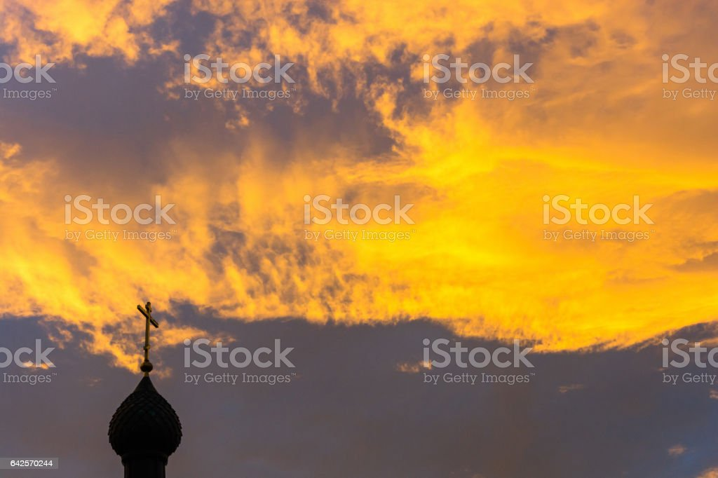 Church domes on the background of the orange-yellow sky. stock photo