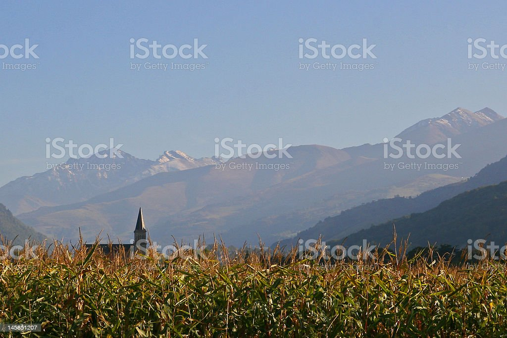 Church in a corn field with mountains background royalty-free stock photo