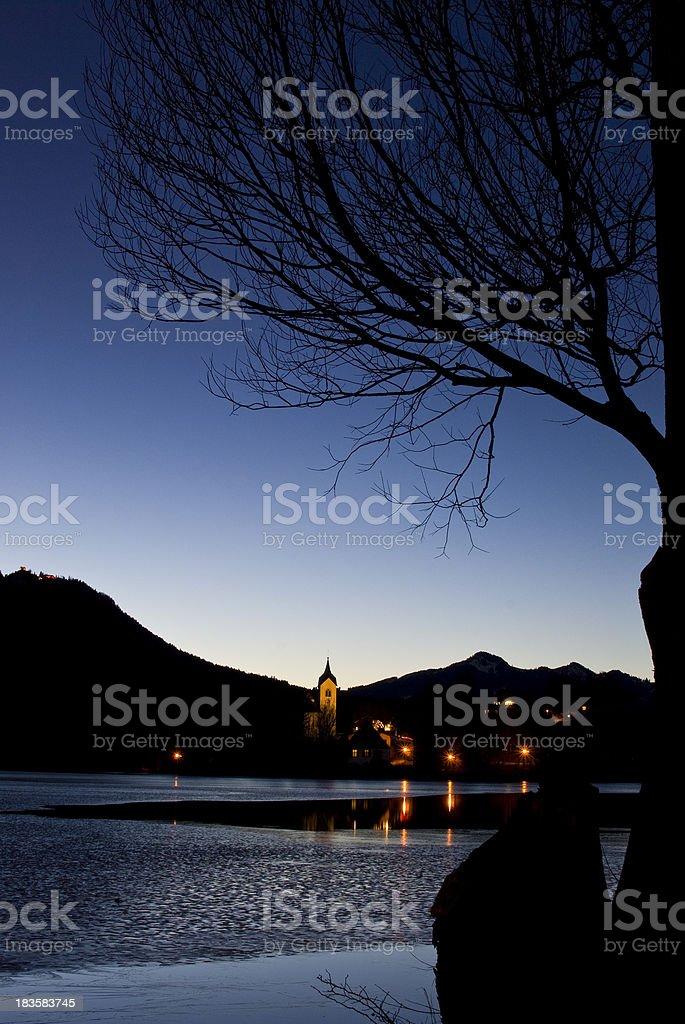 Church near lake through tree in the night - Germany stock photo