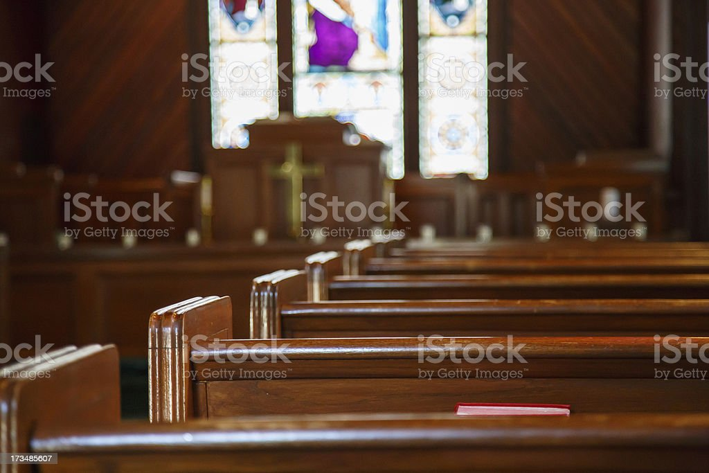 Church Pews with Stained Glass Beyond Pulpit stock photo