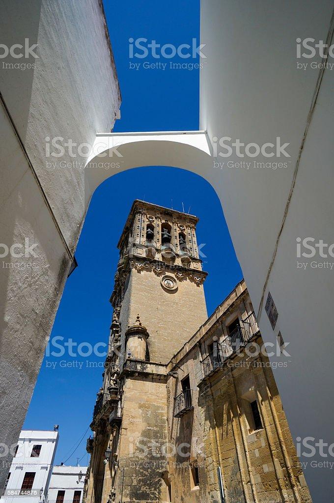 Church seen through an Arch in Arcos de la Frontera stock photo