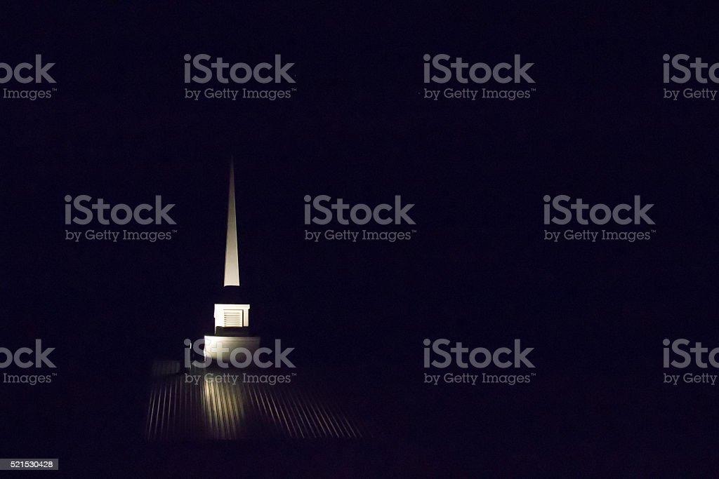 Church spire lit up at night stock photo