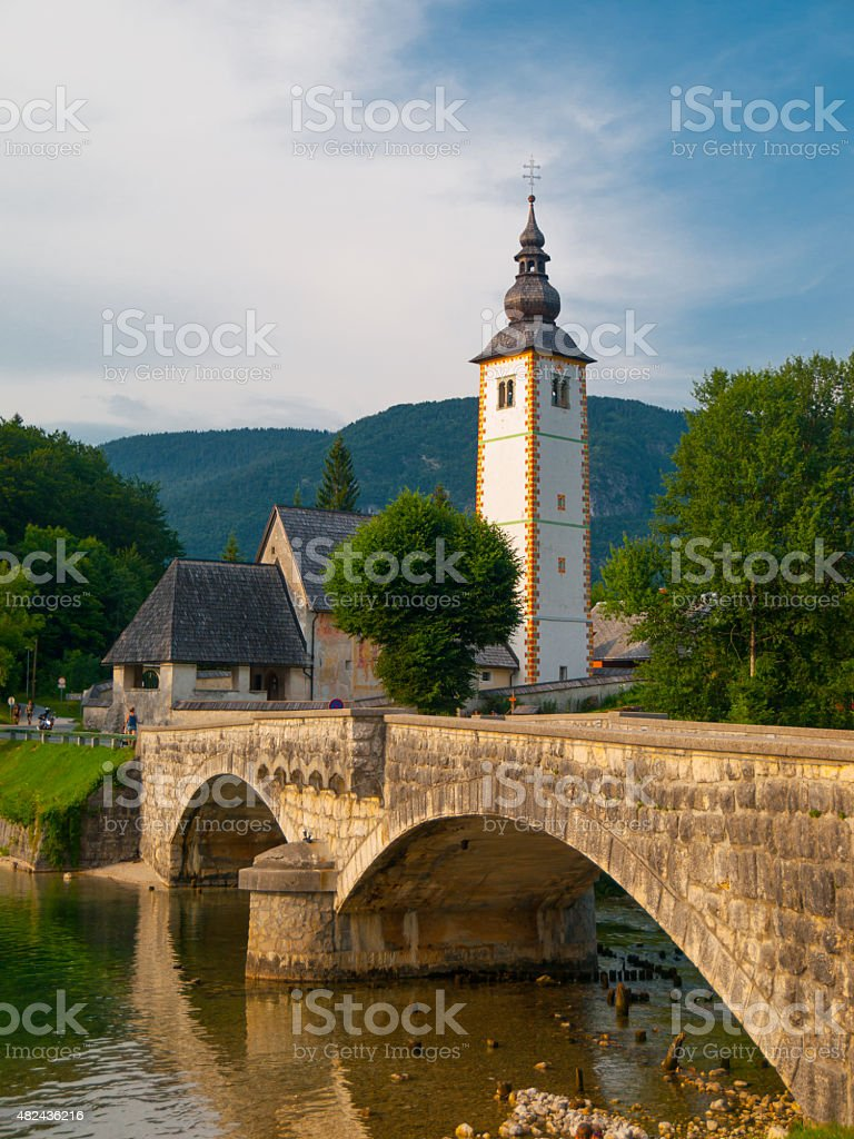 Church tower and stone bridge at Lake Bohinj stock photo