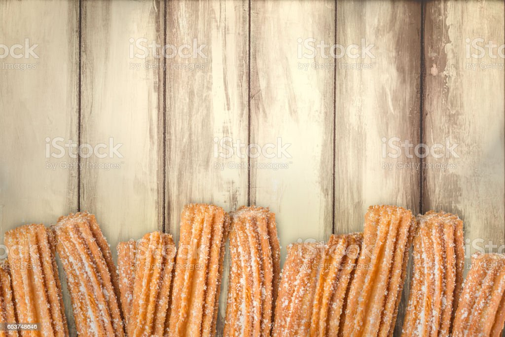 Churros arranged in row on wooden background stock photo