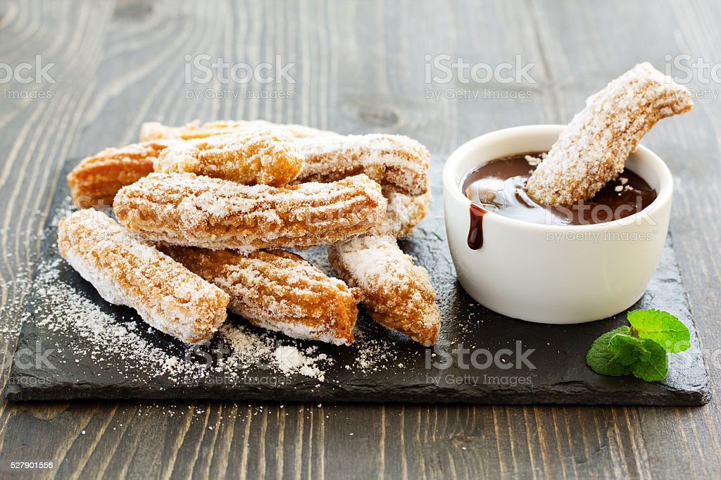 Churros with hot chocolate and powdered sugar. stock photo