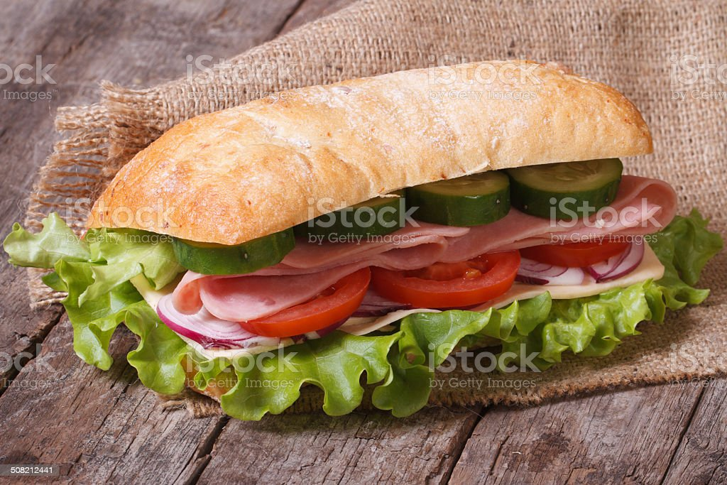 ciabatta sandwich with ham and vegetables on an old wooden stock photo