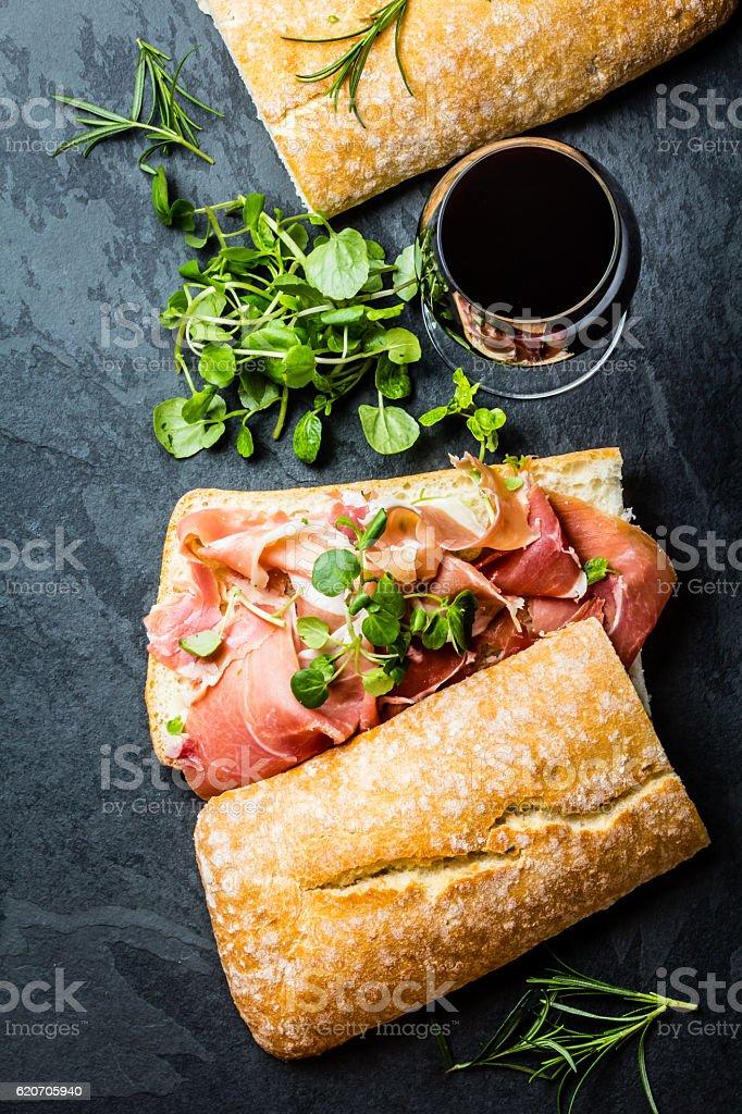 Ciabatta sandwich with jamon ham, arugula. red wine, slate background stock photo