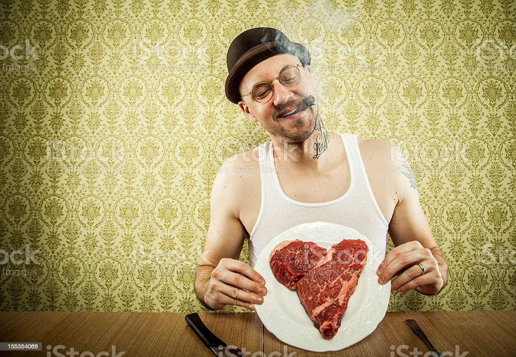 Cigar Puffing Man Displaying Heart Shaped Steak on White Plate royalty-free stock photo