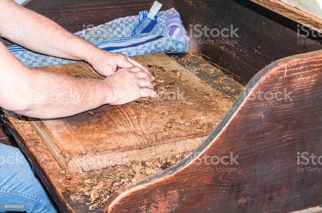 Cigar roll, tobacco leaf and cigar on a table stock photo