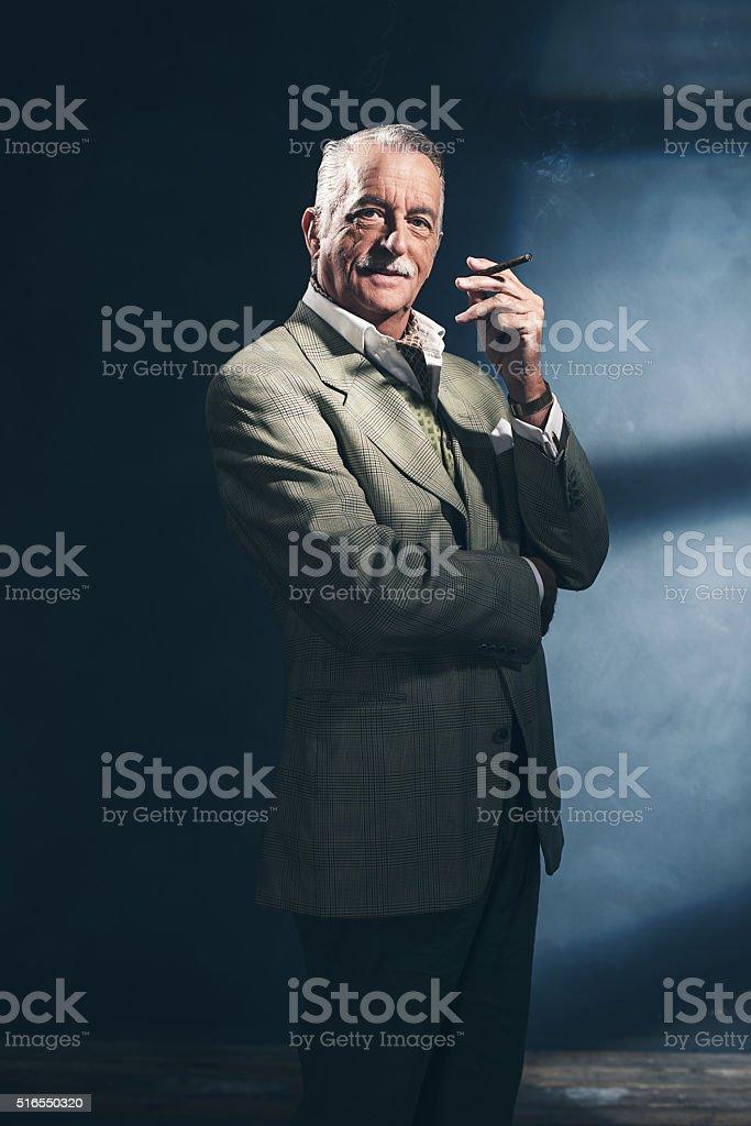 Cigar smoking retro 1940 senior businessman. Studio shot. stock photo