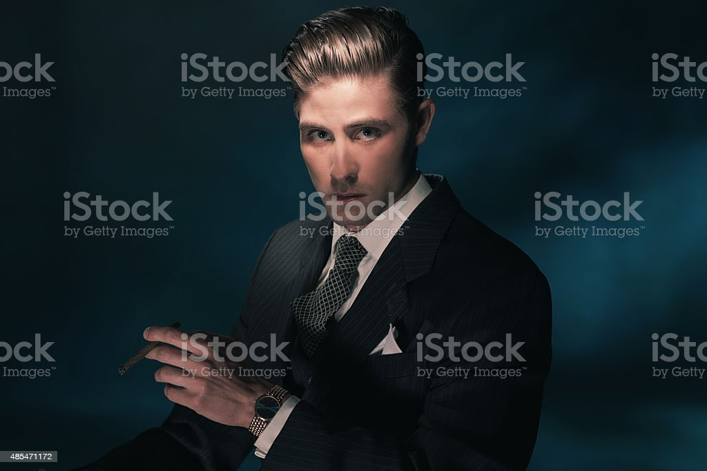 Cigar smoking vintage businessman in suit and tie. stock photo