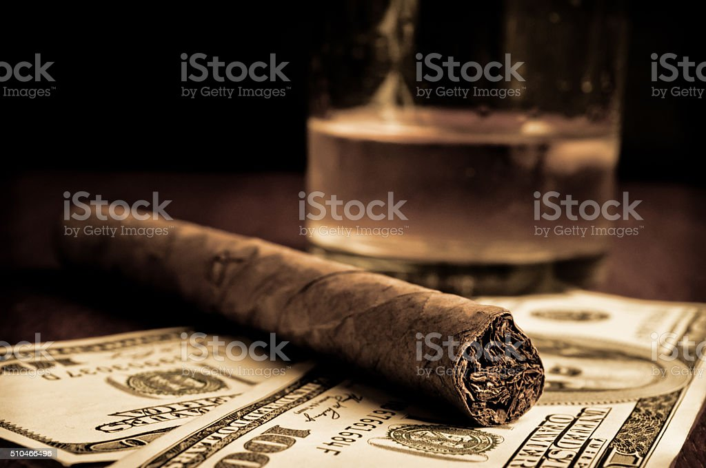 Cigar, whiskey and Dollars stock photo