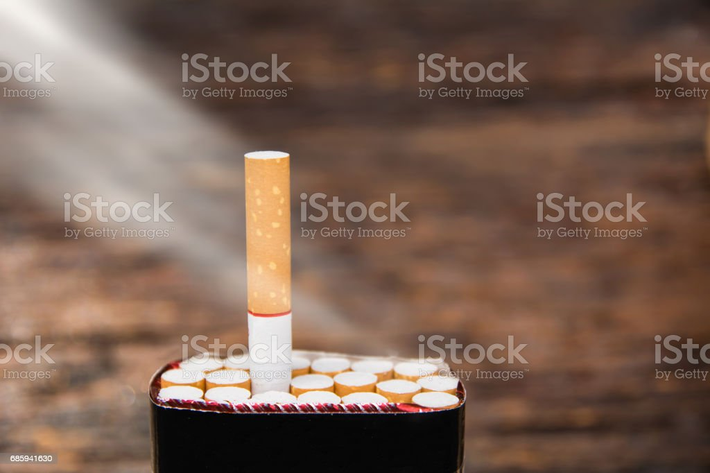cigarette and cigarette box with sun ray on wooden background stock photo