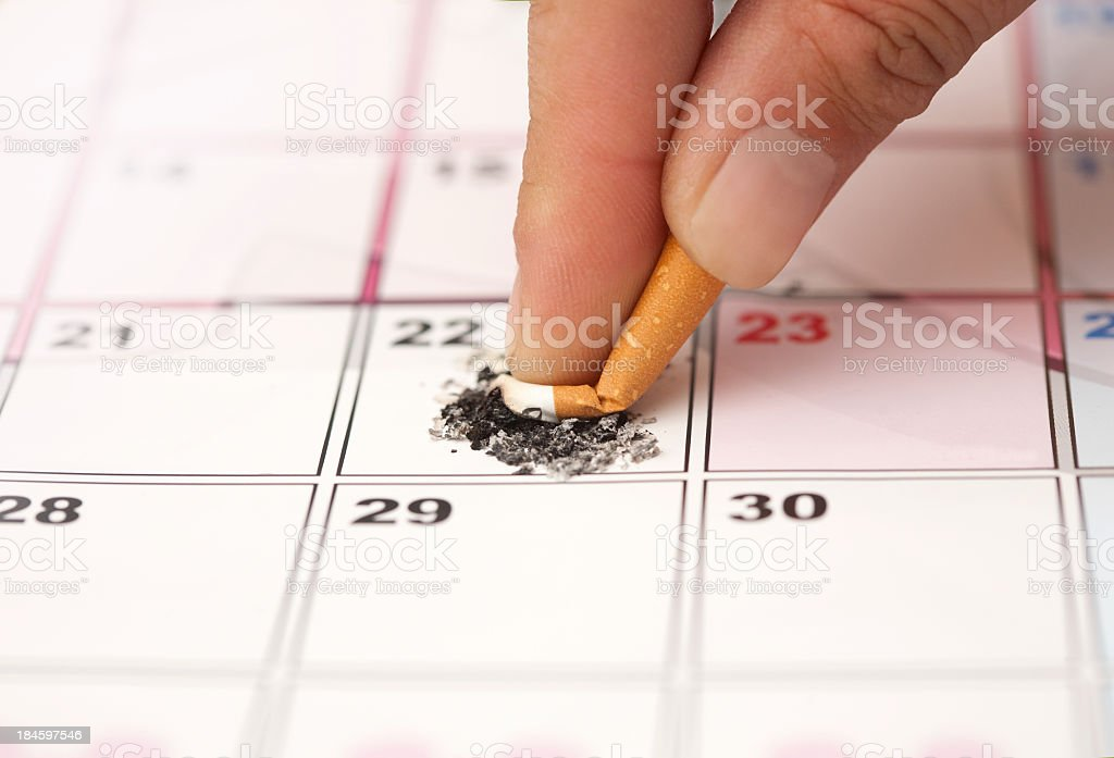 Cigarette being stubbed out on a calendar date royalty-free stock photo