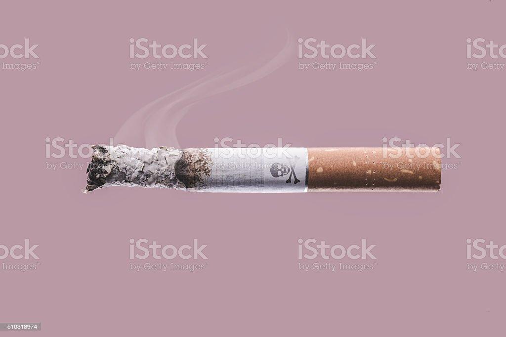 Cigarette burning with skull and bones symbol stock photo