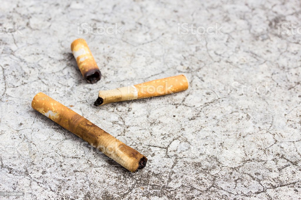 Cigarette butt discarded on the cement floor stock photo
