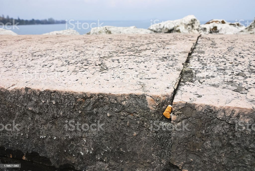 cigarette butt in a brick column stock photo