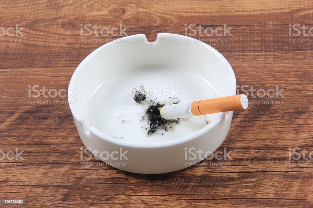 Cigarette butt in ashtray stock photo