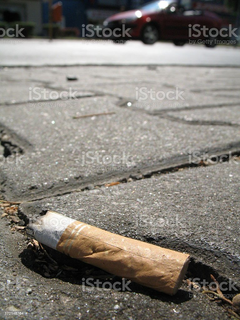 A cigarette butt on the pavement royalty-free stock photo