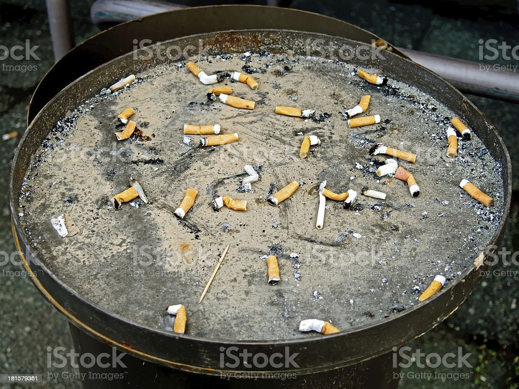 Cigarette butts in a outdoor ashtray royalty-free stock photo