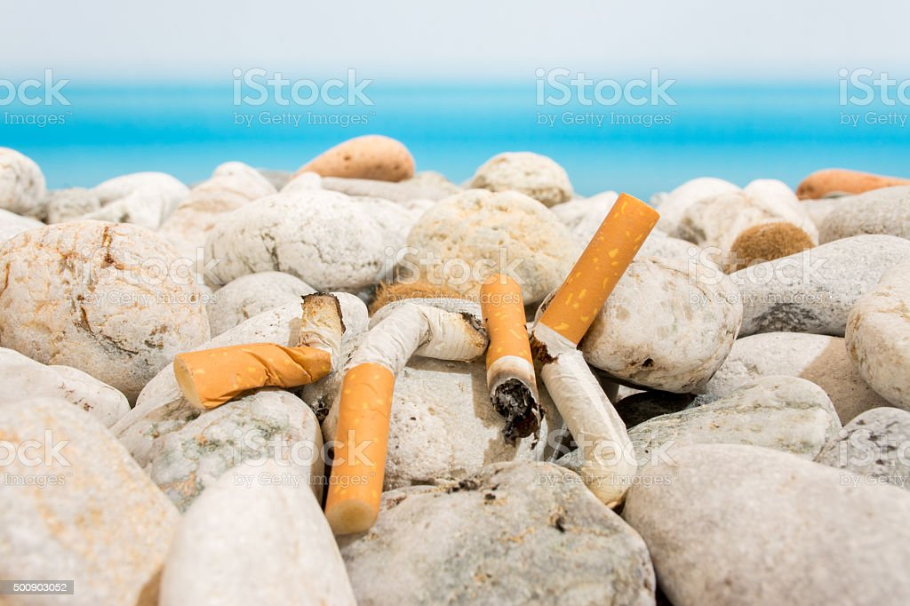 Cigarette butts on the beach stock photo