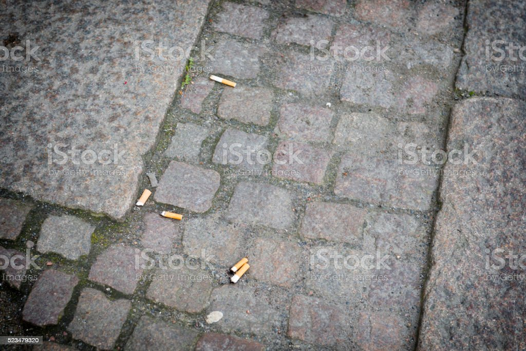 Cigarette butts on the pavement stock photo