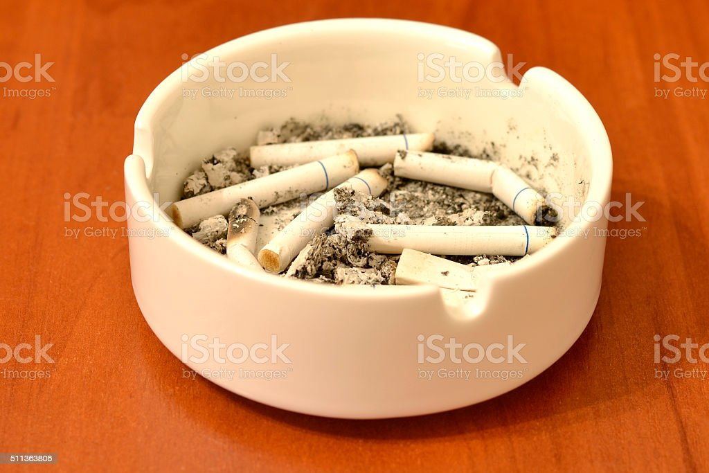 Cigarette in ashtray on table stock photo