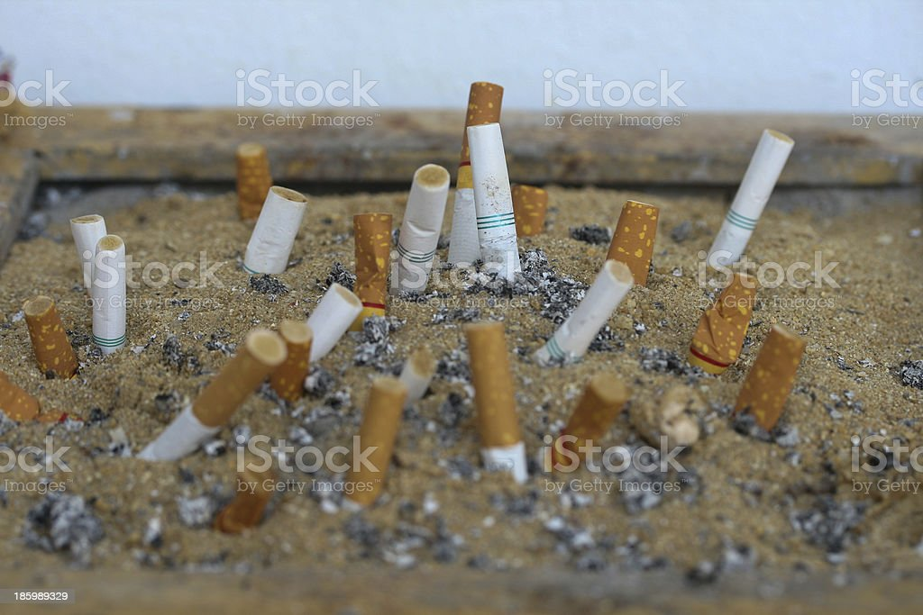 Cigarette in sand on ashtray royalty-free stock photo